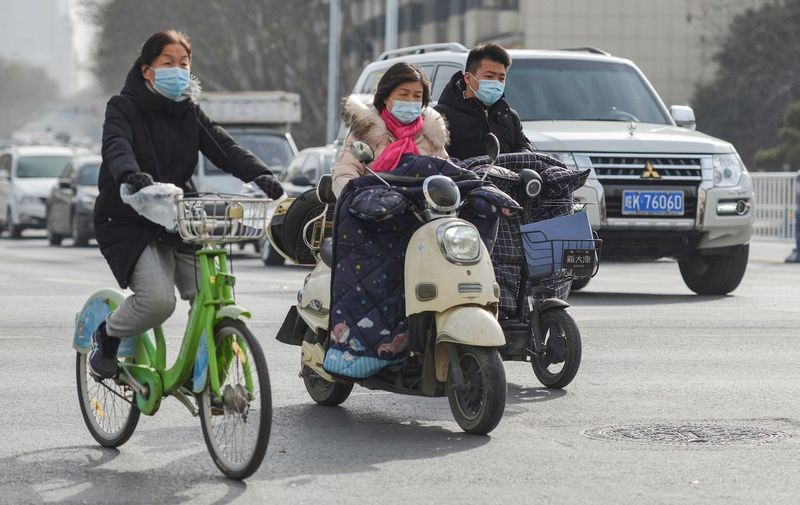 People wearing face masks as a preventive measure against the spread of coronavirus ride electric scooters and bicycle. The WHO (World Health Organization) team of international researchers that arrived in the central Chinese city of Wuhan on Thursday hopes to find clues to the origin of the COVID-19 pandemic. Daily Life in Fuyang, China - 15 Jan 2021,Image: 583602672, License: Rights-managed, Restrictions: , Model Release: no