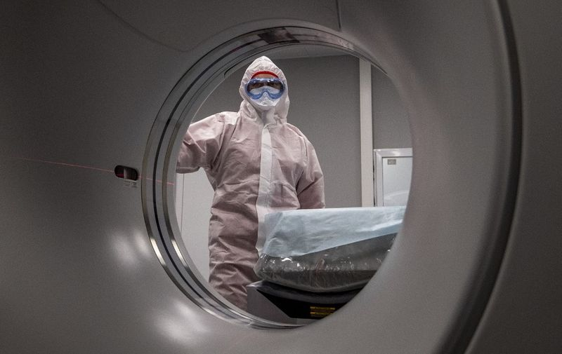 A medical worker wearing protective equipment stands by a computed tomography (CT) scanner at a new hospital built to treat coronavirus patients outside the village of Golokhvastovo  on April 23, 2020. - The 800-bed hospital, 70 kilometres (40 miles) south of Moscow, was inspired by a coronavirus facility in the Chinese province of Wuhan, officials said, and was built in a month. The complex is equipped with a lab and a dormitory for staff. (Photo by Yuri KADOBNOV / AFP)