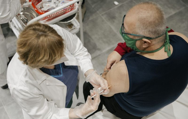 A man receives a Pfizer-BioNTech Covid-19 vaccine at a clinic in Belgrade on January 13, 2021. - Serbia has started vaccinating against the novel coronavirus Covid-19 with Pfizer-BioNTech jab on December 24, 2020. The health authorities have also authorised, on December 31, the import of the first doses of the Russian vaccine Sputnik V. (Photo by Vladimir Zivojinovic / AFP)