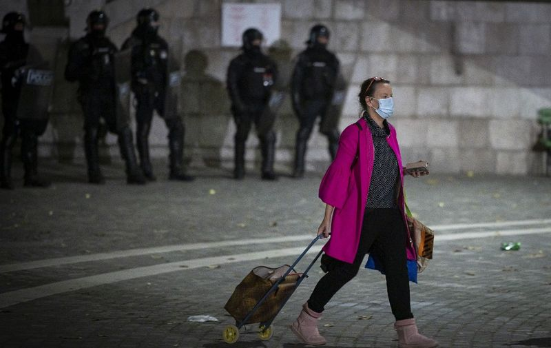 A woman with a shopping trolley walks past police officers wearing anti-riot gear as protesters clash with police during the rally against government's coronavirus restrictions in Ljubljana on November 5, 2020. (Photo by Jure Makovec / AFP)