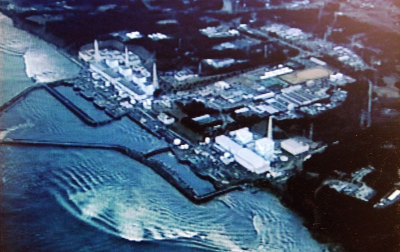 "HANDOUT RESTRICTED TO EDITORIAL USE - MANDATORY CREDIT ""AFP PHOTO / HO / MINISTRY OF LAND, INFRASTRUCTURE AND TOURISM VIA JIJI PRESS"" - NO MARKETING NO ADVERTISING CAMPAIGNS - DISTRIBUTED AS A SERVICE TO CLIENTS  This handout picture, released from Ministry of Land, Infrstructure and Tourism on March 23, 2011 shows an aerial view of Tokyo Electric Power Co (TEPCO) Fukushima No.1 nuclear power plant and a tsunami rushing to the plant on March 11.     AFP PHOTO / HO / MINISTRY OF LAND, INFRASTRUCTURE AND TOURISM VIA JIJI PRESS (Photo by HO / JIJI PRESS / AFP) / - Japan OUT"