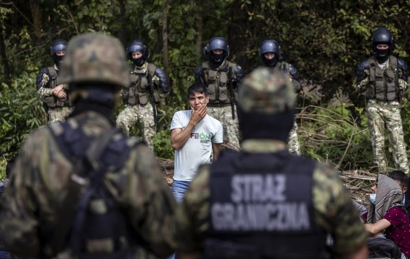 A member of a group of migrants believed to be from Afghanistan stands as he tries to confirm their will to apply for international protection in Poland in the presence of Polish volounteer lawyers, press members and Polish Parliament deputies, in the small village of Usnarz Gorny near Bialystok, northeastern Poland, located close to the border with Belarus, on August 20, 2021. - The fate of a group of 32 bedraggled migrants stranded at a makeshift encampment on the border between Belarus and Poland for nearly two weeks has sparked a heated debate in Poland. The sight of the migrants, who are believed to be from Afghanistan, stuck between armed Belarusian officers and Polish soldiers just a few metres away has moved many Poles. (Photo by Wojtek RADWANSKI / AFP)