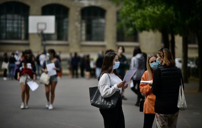 Pupils wearing masks talk in the courtyard as they arrive to learn the outcome of the baccalaureate at the Jean-de-La-Fontaine highschool in the 16th arrondissement of Paris on July 7, 2020. (Photo by Martin BUREAU / AFP)