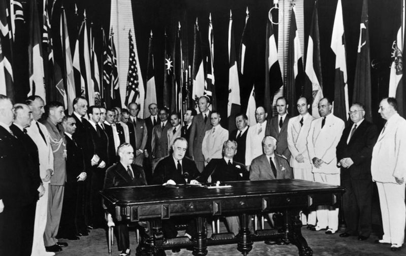 US President Franklin D. Roosevelt (2nd L) reads a statement among representatives of United Nations members during their formal pledge to cooperate for victory and to adhere to the Atlantic Charter in Washington D.C. 01 January 1942.  AFP PHOTO (Photo by HO / UNITED NATIONS / AFP)