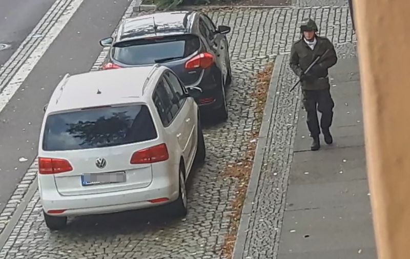 In this screenshot taken from a video by ATV-Studio Halle, a man walks with a gun in the streets of Halle an der Saale, eastern Germany, on October 9, 2019. - At least two people were shot dead on a street in Halle, police said, with witnesses saying that a synagogue was among the gunmen's targets as Jews marked the holy day of Yom Kippur. One suspect was captured but with a manhunt ongoing for other perpetrators, security has been tightened in synagogues in other eastern German cities while Halle itself was in lockdown. (Photo by Andreas Splett / ATV-Studio Halle / AFP) / RESTRICTED TO EDITORIAL USE