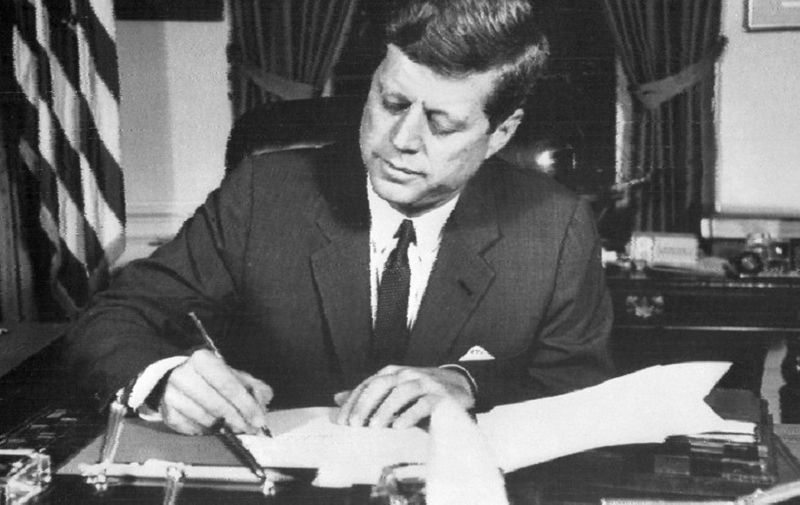 """(FILES) This file photo taken on October 24, 1962 shows US President John Fitzgerald Kennedy signing the order of naval blockade of Cuba at the White House in Washington, DC, during the Cuban missiles crisis.  The National Archives will release 2,800 records on October 26, 2017 about the assassination of president John F. Kennedy, but is delaying the publication of some """"sensitive"""" files, administration officials said. President Donald Trump agreed to delay the release of some documents related to the November 22, 1963 assassination at the request of the CIA, FBI and other agencies, the officials said. / AFP PHOTO / AFP FILES / -"""