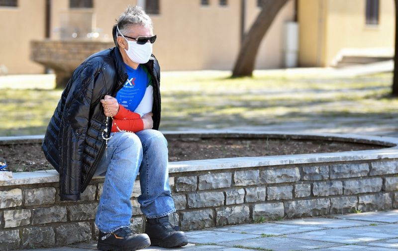 Italian citizen Gino who lives in Bosnia, prays alone in front of the St Jacob church, usually riddled with thousands of Catholic believers, at Marian pilgrimage site, in the southern Bosnian town of Medjugorje, on April 7, 2020 during a lockdown to stop the spread of COVID-19 (novel coronavirus). - Ever since the Virgin Mary was said to appear before six teenagers on a hill in Bosnia four decades ago, pilgrims have flocked to the town of Medjugorje, eager to witness a miracle. (Photo by ELVIS BARUKCIC / AFP)