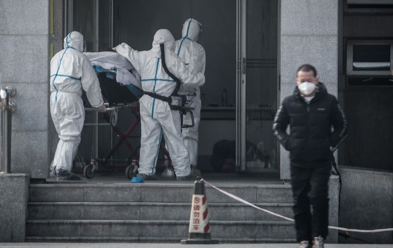 Medical staff members carry a patient into the Jinyintan hospital, where patients infected by a mysterious SARS-like virus are being treated, in Wuhan in China's central Hubei province on January 18, 2020. - The true scale of the outbreak of a mysterious SARS-like virus in China is likely far bigger than officially reported, scientists have warned, as countries ramp up measures to prevent the disease from spreading. (Photo by STR / AFP) / China OUT