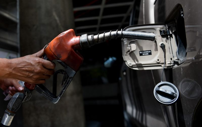 """An employee pumps petrol into a vehicle in Caracas where people are queueing at gas stations on August 17, 2018 for the uncertainty about the price and availability of gasoline from Monday on, when the new currency with five fewer zeros starts circulating in Venezuela. - President Nicolas Maduro announced on August 13 that Venezuela's dirt-cheap fuel will be available only to people with a special government aid card that the opposition has denounced as a tool for controlling people. People who want to keep benefiting from subsidized gas prices in this oil-rich nation must register their vehicles by Friday using the so-called """"carnet de la patria,"""" or fatherland card, which provides access to government assistance. (Photo by Federico PARRA / AFP)"""