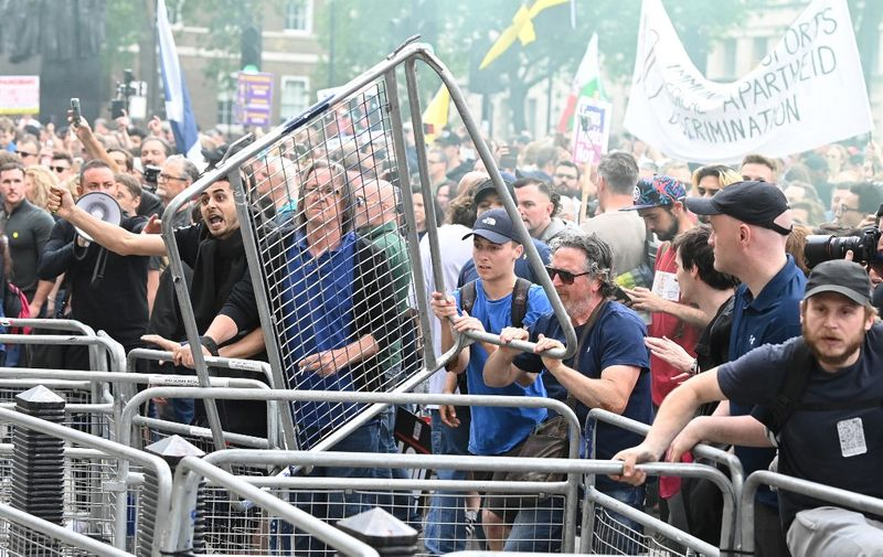 People throw fencing during an anti-Vaccine and anti-lockdown demonstration outside Downing street in central London, on June 26, 2021. (Photo by DANIEL LEAL-OLIVAS / AFP)