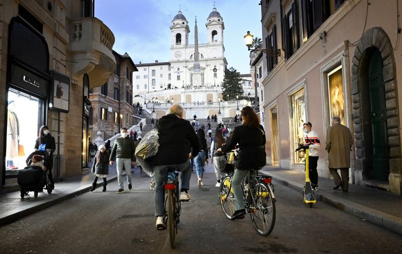 """People cycle across the Via dei Condotti luxury shopping street towards Piazza di Spagna and the Spanish steps in downtown Rome on March 13, 2021 before the government tightens restrictions across most of the country from March 15, facing a """"new wave"""" after it recorded almost 26,000 new Covid-19 cases and another 373 deaths on March 11. (Photo by Alberto PIZZOLI / AFP)"""