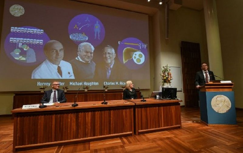 Thomas Perlmann (R), the Secretary of the Nobel Committee, speaks to announce the winners of the 2020 Nobel Prize in Physiology or Medicine (On screen L-R) American Harvey Alter, Briton Michael Houghton and American Charles Rice, as Nobel Committee members Patrik Ernfors (L) and Gunilla Karlsson Hedestam look on, during a press conference at the Karolinska Institute in Stockholm, Sweden, on October 5, 2020. - Americans Harvey Alter and Charles Rice as well as Briton Michael Houghton win the 2020 Nobel Medicine Prize for the discovery of Hepatitis C virus. (Photo by Jonathan NACKSTRAND / AFP)