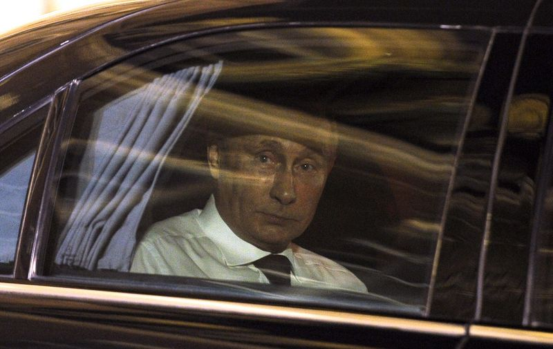 Russian President Vladimir Putin looks on from his car as he leaves the Elysee Palace following his meeting and dinner with his French counterpart in Paris on June 5, 2014. Russian President Vladimir Putin met for talks with French President Francois Hollande, as world leaders engaged in a bout of shuttle diplomacy over Ukraine ahead of D-Day ceremonies. AFP PHOTO / FRED DUFOUR (Photo by FRED DUFOUR / AFP)