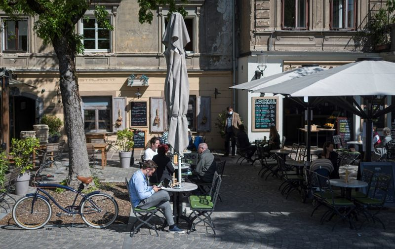 People sit at a caffe terrace in Ljubljana, on May 4, 2020, on the first day of the lockdown ease amid the Covid-19 pandemic caused by the novel coronavirus. - Bars and hairdressers are allowed to reopen from May 4, 2020 in Slovenia under strict hygienic and distancing rules. (Photo by Jure Makovec / AFP)
