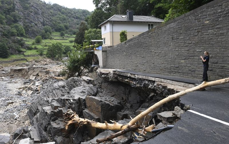 A policewoman takes a picture of a crater whera a road that has sunken in the city of  Altenahr, Rhineland-Palatinate, western Germany, on July 19, 2021, after devastating floods hit the region. - The German government on July 19, 2021 pledged to improve the country's under-fire warning systems as emergency services continued to search for victims of the worst flooding in living memory, with at least 165 people confirmed dead. (Photo by CHRISTOF STACHE / AFP)
