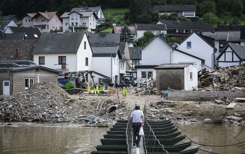A man walks across a temporary bridge in the wine village of Rech near Dernau on the river Ahr, western Germany, on July 30, 2021, weeks after heavy rain and floods caused major damage in the Ahr region. - At least 180 people died when severe floods pummelled western Germany over two days in mid-July, raising questions about whether enough was done to warn residents ahead of time. People are still missing after torrents of water ripped through entire towns and villages, destroying bridges, roads, railways and swathes of housing. (Photo by Bernd Lauter / AFP)