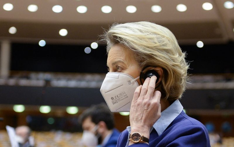 European Commission President Ursula Von Der Leyen adjusts her earphone during a debate on the European Union's vaccine strategy at the European Parliament in Brussels, on February 10, 2021. - Leaders of the European Union have been engaged in bitter public rows with pharmaceutical firms over supply shortages, as they faced public anger and scrutiny over slow vaccination rollouts in member states. (Photo by JOHANNA GERON / POOL / AFP)