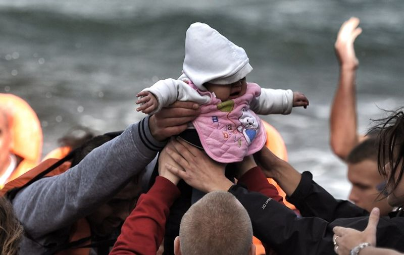 TOPSHOTS A baby is carried by migrants and asylum seekers as they arrive to the Greek island of Lesbos after crossing the Aegean sea from Turkey on October 31, 2015. AFP PHOTO / ARIS MESSINIS