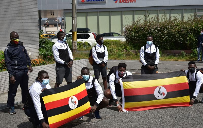 Members of the Uganda Olympics team pose for a photo call as they arrive at a hotel in Izumisano city, Osaka Prefecture on June 20, 2021. (Photo by STR / JIJI PRESS / AFP) / Japan OUT