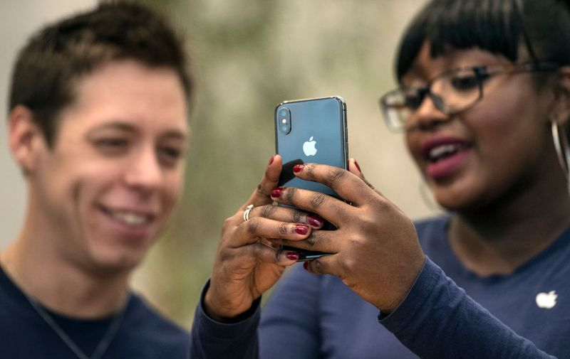 LONDON, ENGLAND - NOVEMBER 03: Staff members view the new iPhone X in the Apple store upon its release in the U.K, on November 3, 2017 in London, England. The iPhone X is positioned as a high-end, model intended to showcase advanced technologies such as wireless charging, OLED display, dual cameras and a face recognition unlock system.  (Photo by Carl Court/Getty Images)