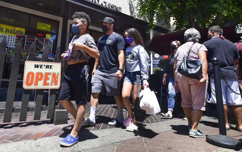 Face masks continue to be worn as people walk past restaurants open for business in Los Angeles on June 14, 2021, one day before the state full reopening of its economy since the first statewide shutdown in March 2020 due to the coronavirus pandemic. - California is removing nearly all pandemic restrictions on June 15, with no mandatory capacity restrictions or social distancing requirements for those who have been vaccinated. (Photo by Frederic J. BROWN / AFP)