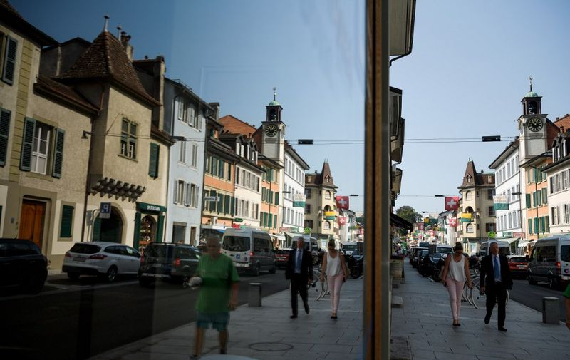 "The main street of the city of Rolle is seen refelected in a shop window on August 29, 2017. - ""Everyone knows that Jean- Luc Godard is here, but nobody knows who Godard really is,"" says Denys Jaquet, mayor of Rolle, a small town of 6,000 inhabitants on the shores of Lake Geneva. The director of ""Pierrot le Fou"" or ""Sauve qui peut (la vie)"" has been installed since 1977 in Rolle, near the town of Nyon where he spent part of his childhood. He lives with his wife, director Anne-Marie Mieville. (Photo by Fabrice COFFRINI / AFP)"