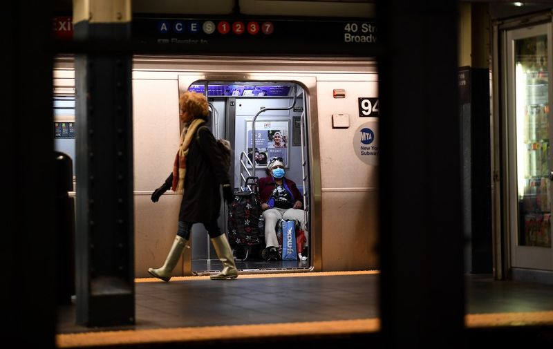"""A woman with a mask sits in a subway at the Plattform at Times Square on March 13, 2020  in New York City. - The World Health Organization said March 13, 2020 it was not yet possible to say when the COVID-19 pandemic, which has killed more than 5,000 people worldwide, will peak. """"It's impossible for us to say when this will peak globally,"""" Maria Van Kerkhove, who heads the WHO's emerging diseases unit, told a virtual press conference, adding that """"we hope that it is sooner rather than later"""". (Photo by Johannes EISELE / AFP)"""