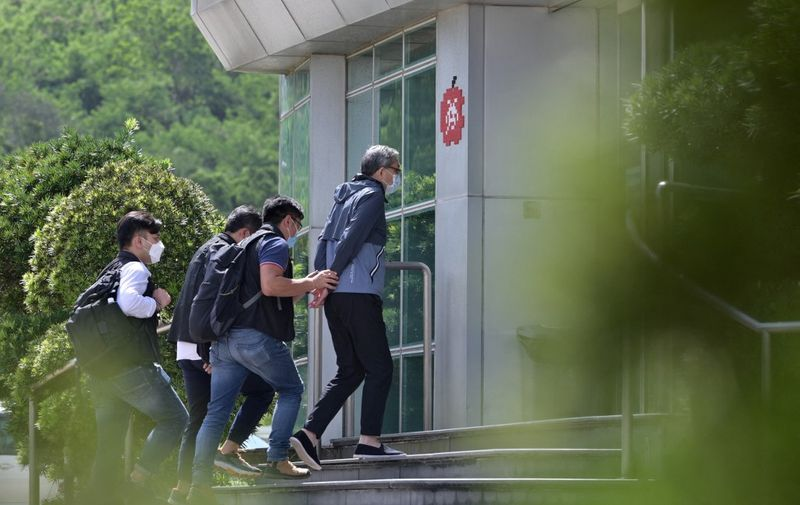 Cheung Kim Hung (C), CEO and Executive Director of Next Digital Ltd, is escorted by police into the Apple Daily newspaper offices in Hong Kong on June 17, 2021. (Photo by Anthony WALLACE / AFP)