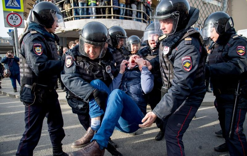 Riot police officers detain a protester during an unauthorised anti-corruption rally in central Moscow on March 26, 2017. Thousands of Russians demonstrated across the country on March 26 to protest at corruption, defying bans on rallies which were called by prominent Kremlin critic Alexei Navalny -- who was arrested along with scores of others. Navalny called for the protests after publishing a detailed report this month accusing Prime Minister Dmitry Medvedev of controlling a property empire through a shadowy network of non-profit organisations.   / AFP PHOTO / Alexander UTKIN