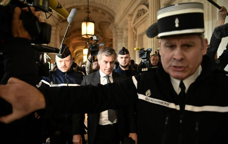 Gendarmes escort French former budget minister Jerome Cahuzac (C) as he leave the Paris courthouse following his tax fraud and money laundering trial's verdict on December 8, 2016.  Former French budget minister Jerome Cahuzac, whose brief in government was to crack down on tax dodgers, was sentenced to three years in prison on December 8 for tax fraud and money laundering. / AFP PHOTO / PHILIPPE LOPEZ