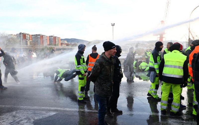 Police use water cannon and tear gas to disperse the dockers blocking gate 4 while demonstrating against the Green Pass in the port of Trieste following a three-day demonstration against a new mandatory workplace Covid-19 pass, on October 18, 2021. - The police cannons target hundreds of remaining protestors and port workers who have been blocking one of the port entrances since October 15, to protest against Italy's so-called Green Pass. (Photo by STRINGER / ANSA / AFP) / Italy OUT