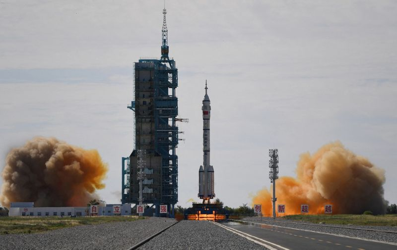 A Long March-2F carrier rocket, carrying the Shenzhou-12 spacecraft and a crew of three astronauts, lifts off from the Jiuquan Satellite Launch Centre in the Gobi desert in northwest China on June 17, 2021, the first crewed mission to China's new space station. (Photo by GREG BAKER / AFP)