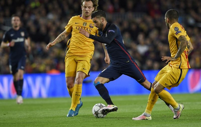 Barcelona's Croatian midfielder Ivan Rakitic (L) and Barcelona's Brazilian defender Dani Alves (R) vie with Atletico Madrid's Belgian midfielder Yannick Ferreira Carrasco during the UEFA Champions League quarter finals first leg football match FC Barcelona vs Atletico de Madrid at the Camp Nou stadium in Barcelona on April 5, 2016. / AFP PHOTO / LLUIS GENE