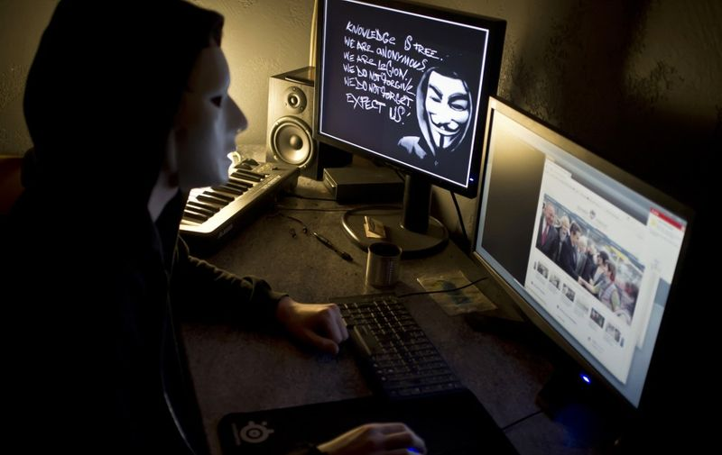 A masked hacker, part of the Anonymous group, hacks the French presidential Elysee Palace website on January 20, 2012 near the eastern city of Lyon. Anonymous, which briefly knocked the FBI and Justice Department websites offline in retaliation for the US shutdown of file-sharing site Megaupload, is a shadowy group of international hackers with no central hierarchy. On the left screen, an Occupy mask is seen. AFP PHOTO / JEAN-PHILIPPE KSIAZEK (Photo by JEAN-PHILIPPE KSIAZEK / AFP)