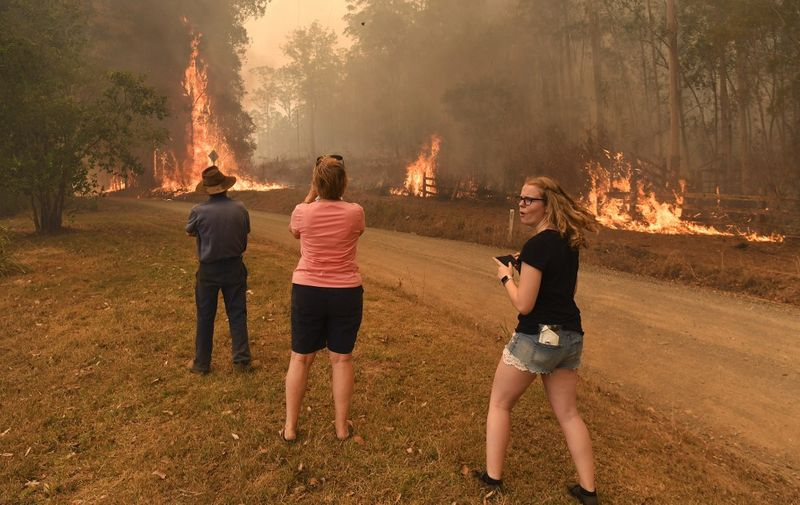 People watch as the fire front approaches their home at Nabiac, some 350kms north of Sydney, on November 15, 2019. - The death toll from devastating bushfires in eastern Australia has risen to four after a man's body was discovered in a scorched area of bushland, police said on November 14. (Photo by WILLIAM WEST / AFP)