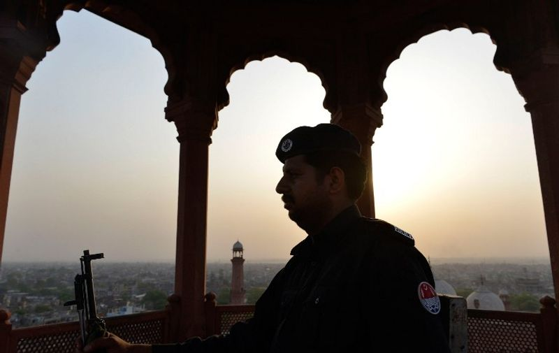 A Pakistani policeman stands guard during evening prayers at the historical Badshahi mosque in Lahore on April 25, 2015, led by the Saudi Arabian Imam of the Grand Mosque in Mecca Sheikh Khalid al Ghamdi. Sheikh Khalid al Ghamdi arrived in Pakistan to meet with senior leaders of the ruling Pakistan Muslim League-Nawaz (PML-N). AFP PHOTO / Arif ALI / AFP / Arif Ali
