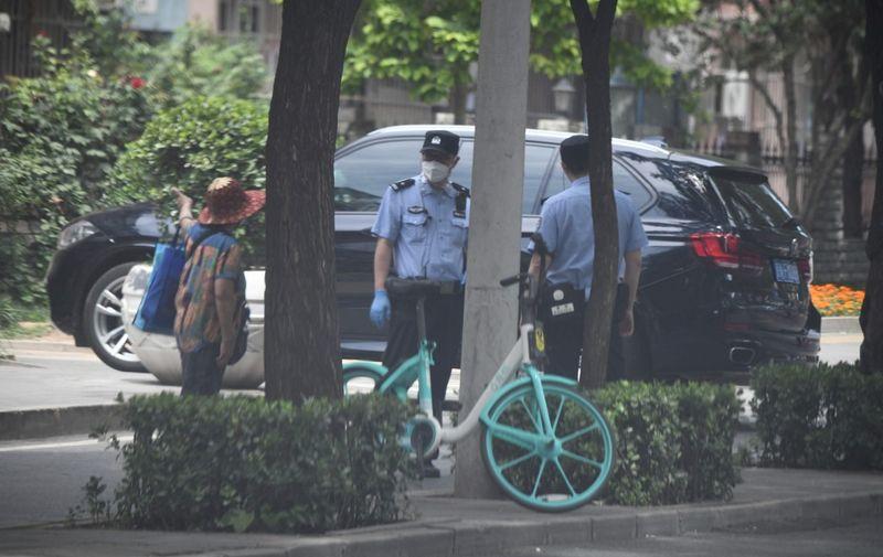 Policemen wearing face masks are seen near a residential area under lockdown near Yuquan East Market in Beijing on June 15, 2020. - China locks down ten more Beijing neighbourhoods over virus cluster. (Photo by Noel Celis / AFP)