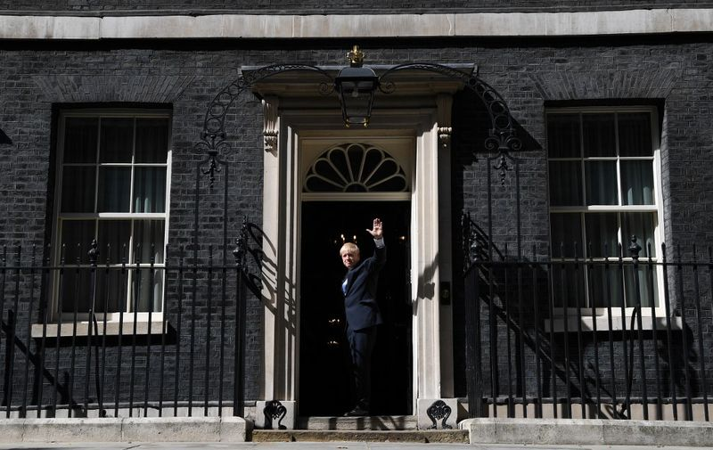 Britain's new Prime Minister Boris Johnson waves on the step of 10 Downing Street in London on July 24, 2019 after giving a speech on the day he was formally appointed British prime minister. - Boris Johnson takes charge as Britain's prime minister on Wednesday, on a mission to deliver Brexit by October 31 with or without a deal. (Photo by Ben STANSALL / AFP)
