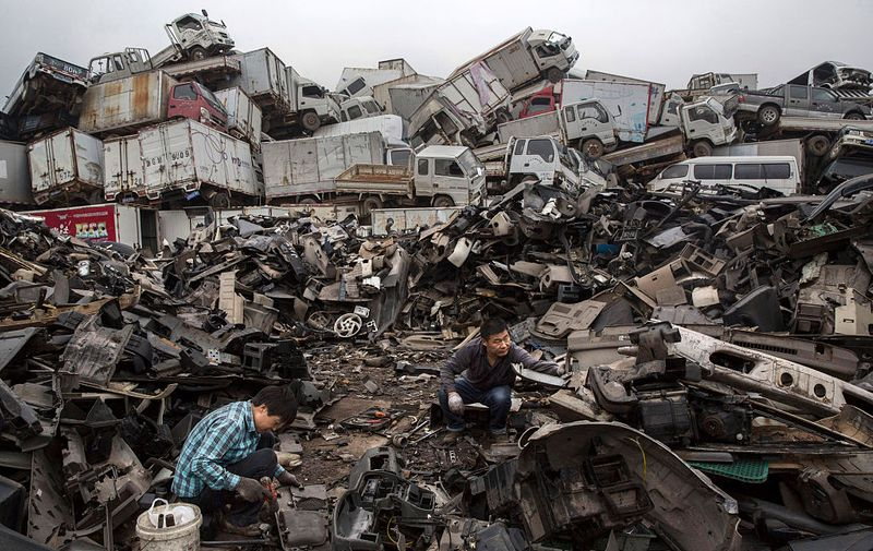 ZHEJIANG, CHINA - SEPTEMBER 25: Chinese labourers dismantle pieces of vehicles taken off the road by authorities at an auto scrapyard on September 25, 2015 in Zhejiang, China. The scrapyard is part of a Chinese government program to remove tens of thousands of polluting vehicles from the nations raods in effort to curb excessive pollution. In 2014, China announced it would cut carbon emissions in the coming decade as part of global agreements on climate change. (Photo by Kevin Frayer/Getty Images)