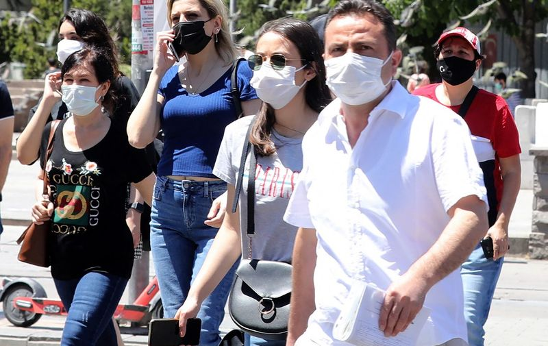People wearing face masks as a protection against the coronavirus (Covid-19) walk in a street in Ankara on May 21, 21021. (Photo by Adem ALTAN / AFP)