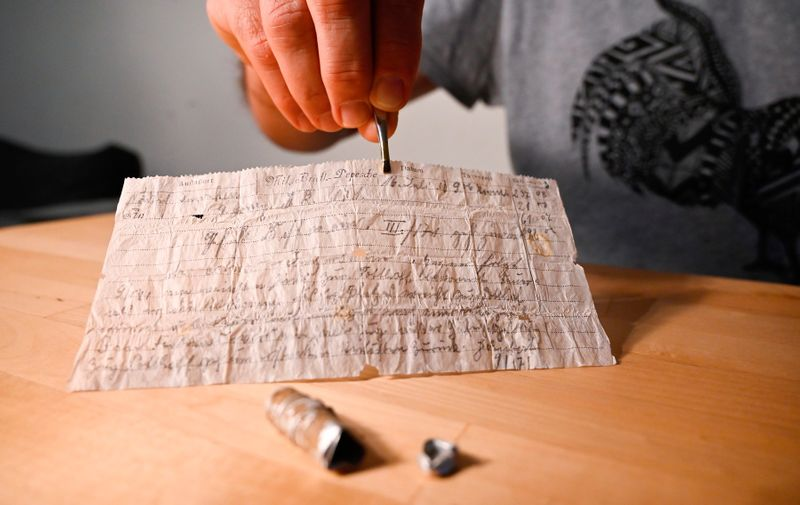 A man shows on November 8, 2020, in Munster, eastern France, a message probably lost by a carrier pigeon in 1910, sent by a German officer and miraculously resurfaced in 2020 in Alsace where it was found by chance.,Image: 568002494, License: Rights-managed, Restrictions: , Model Release: no