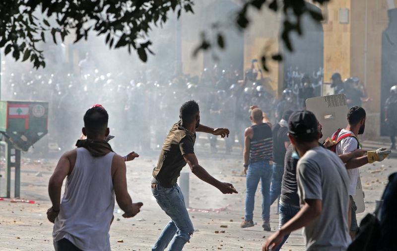 Lebanese protesters hurl rocks towards security forces during clashes in downtown Beirut on August 8, 2020, following a demonstration against a political leadership they blame for a monster explosion that killed more than 150 people and disfigured the capital Beirut. (Photo by STR / AFP)