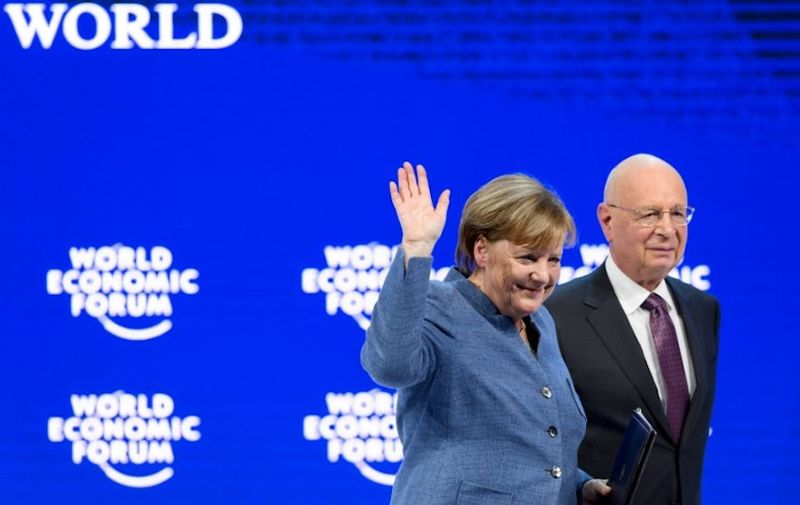 German chancellor Angela Merkel (L) waves next to Founder and Executive Chairman of the World Economic Forum (WEF) Klaus Schwab after addressing the annual World Economic Forum (WEF) on January 24, 2018 in Davos, eastern Switzerland. (Photo by Fabrice COFFRINI / AFP)