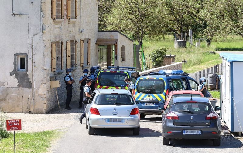 French gendarmes check vehicles during the manhunt of a heavily armed former soldier who allegedly opened fire on officers responding to a domestic violence dispute in Le Lardin-Saint-Lazare, near Sarlat, southwestern France, on May 30, 2021. - French police backed by helicopters hunted on May 30, 2021, for a heavily armed former soldier in southwestern France. Some 210 police officers and four helicopters were searching for the man, who has an electronic tag due to a prior domestic violence conviction, but who was still at large in the woods of the Dordogne region, authorities said. (Photo by Diarmid COURREGES / AFP)