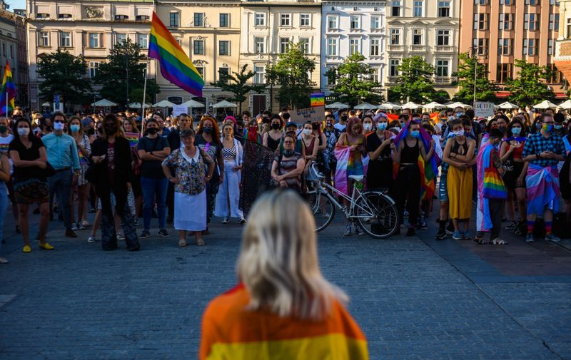 KRAKOW, POLAND - JULY 10: A woman wears a protective face mask and a rainbow flag as she gives a speech during a protest against descrimination of the LGBT community two days before the Presidential elections runoff at Krakow's UNESCO listed Main Square on July 10, 2020 in Krakow, Poland. As the country heads into the July 12 presidential runoff election, the current President Andzrej Duda, backed by the conservative right wing Law and Justice Party proposed a constitutional amendment banning same-sex couples from adopting children. (Photo by Omar Marques/Getty Images)