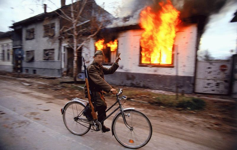 Soldiers and Paramilitaries - A Serbian soldier cycles by a burning house on the destroyed streets of the Croatian city of Vukovar, Nov. 24, 1991. The city was completely destroyed after three months of bombing by Serbian forces., Image: 116177603, License: Rights-managed, Restrictions: Content available for editorial use, pre-approval required for all other uses. This content not available to be downloaded through Quick Pic Not available for license and invoicing to customers located in the Czech Republic. Not available for license and invoicing to customers located in the Netherlands. Not available for license and invoicing to customers located in India. Not available for license and invoicing to customers located in Finland. Not available for license and invoicing to customers located in Italy., Model Release: no, Credit line: Profimedia, Corbis VII