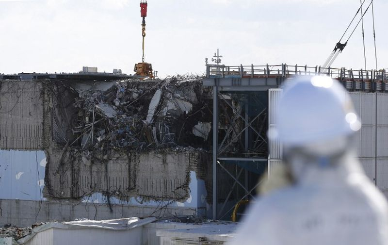 A member of the media, wearing a protective suit and a mask, looks at the No. 3 reactor building during a press tour at Tokyo Electric Power Co's (TEPCO) tsunami-crippled Fukushima Daiichi nuclear power plant in the town of Okuma, Fukushima prefecture on February 10, 2016.  The media tour of the facilities came as Japan readied to mark the fifth anniversary of the March 11, 2011 earthquake and tsunami that caused disastrous meltdowns at the Fukushima nuclear power plant.     AFP PHOTO / POOL / Toru HANAI / AFP / POOL / TORU HANAI
