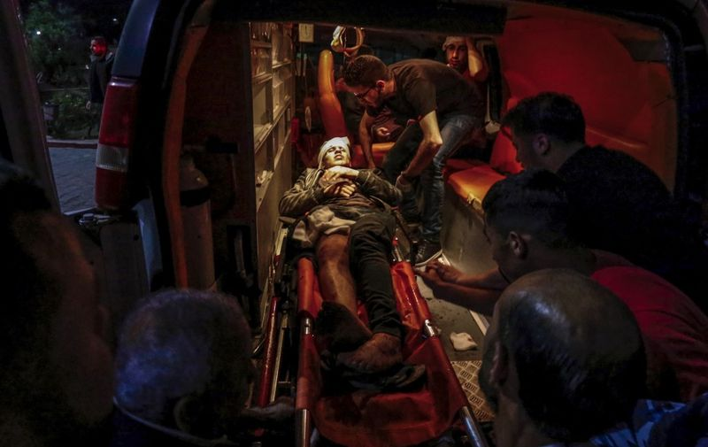 EDITORS NOTE: Graphic content / Paramedics carry the body of a wounded Palestinian at a hospital in Beit Lahia, northern Gaza strip on May 5, 2019. - Three Palestinians including a baby, were killed in Israeli strikes in northern Gaza, the health ministry in the Hamas-run enclave said, as fears of a full conflict grew. (Photo by ANAS BABA / AFP)