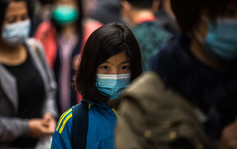 People wearing protective face masks walk along a street in Hong Kong on February 9, 2020, as a preventative measure after a coronavirus outbreak which began in the Chinese city of Wuhan. - The previously unknown virus has caused alarm because of its similarity to SARS (Severe Acute Respiratory Syndrome), which killed hundreds across mainland China and Hong Kong in 2002-2003. (Photo by DALE DE LA REY / AFP)