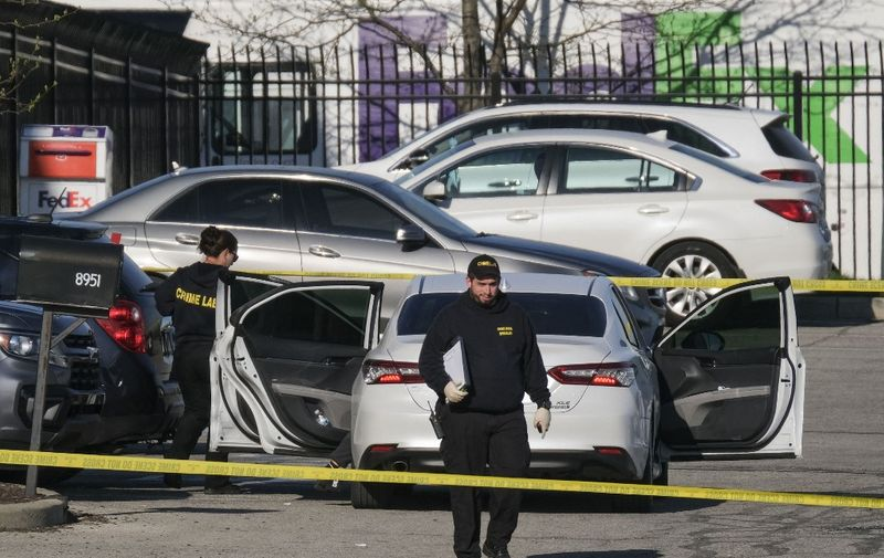 """Crime scene investigators walk through the parking lot of the mass shooting site at a FedEx facility in Indianapolis, Indiana, on April 16, 2021. - A gunman has killed at least eight people at the facility before turning the gun on himself in the latest in a string of mass shootings in the country, authorities said. The incident came a week after President Joe Biden branded US gun violence an """"epidemic"""" and an """"international embarrassment"""" as he waded into the tense debate over gun control, a powerful political issue in the US. (Photo by Jeff Dean / AFP)"""